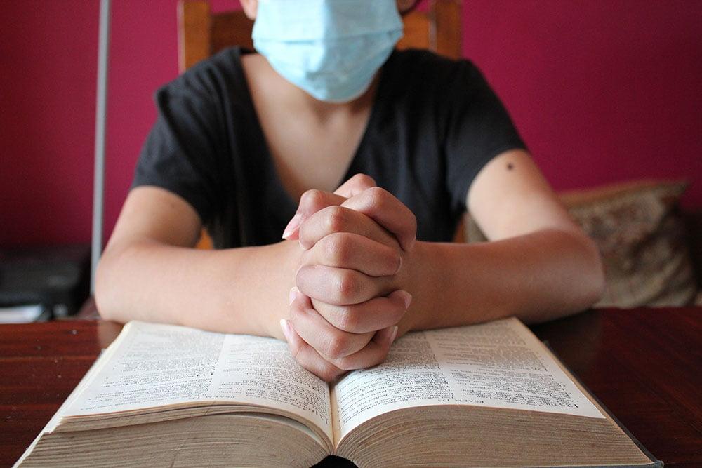 woman wearing mask, praying over bible